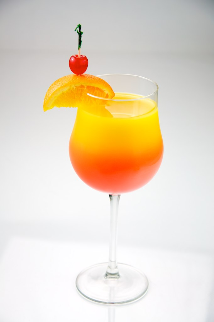 Tequila Sunrise garnished with orange and cherry, shot on a white background.
